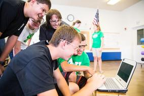 Image of 4H students gathered around a laptop